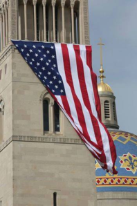 Large flag hangs from the bell tower of the Basilica of the National Shrine of the Immaculate Conception in Wash DC today.  (photo cred: Catholic News Service)